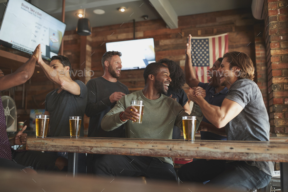 Group Of Friends Watching Game On Screen In Sports Bar - Stock Photo - Images