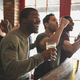 Group Of Male Friends Celebrating Whilst Watching Game On Screen In Sports Bar - PhotoDune Item for Sale