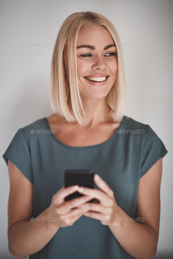 Female entrepreneur smiling while reading texts against a gray background - Stock Photo - Images