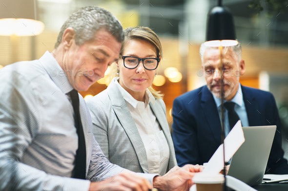 Mature businesspeople discussing paperwork together in a meeting - Stock Photo - Images