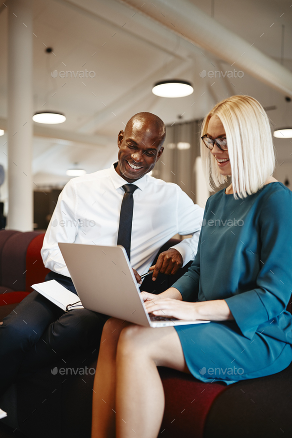 Smiling businesspeople working with a laptop on an office sofa - Stock Photo - Images