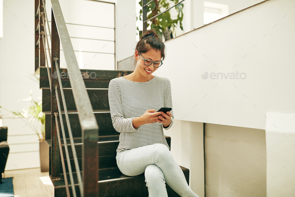 Smiling Asian businesswoman sitting on office stairs reading texts - Stock Photo - Images