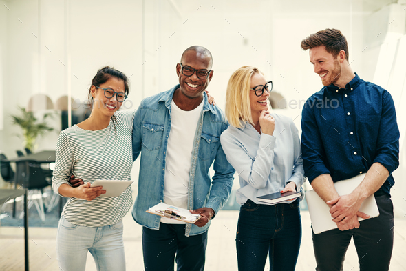 Diverse group of young businesspeople laughing together in an office - Stock Photo - Images