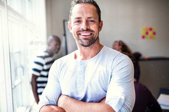Smiling designer standing in an office after a meeting - Stock Photo - Images