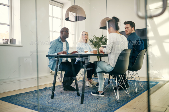 Diverse young businesspeople talking together in an office boardroom - Stock Photo - Images