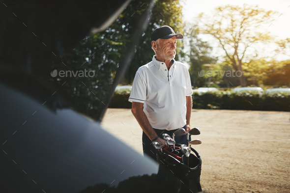 Senior man putting his golf clubs in a car trunk - Stock Photo - Images