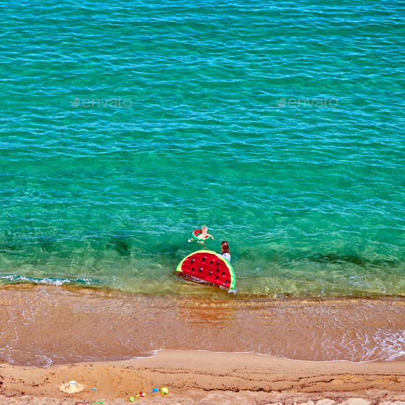 Boy and his mother on beach with inflatable float - Stock Photo - Images