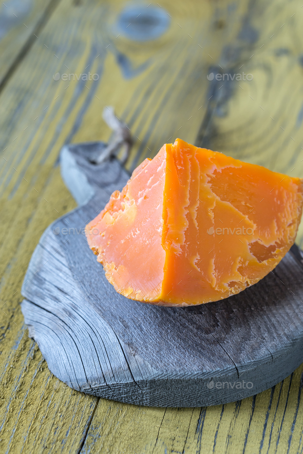 Mimolette cheese on the wooden board - Stock Photo - Images