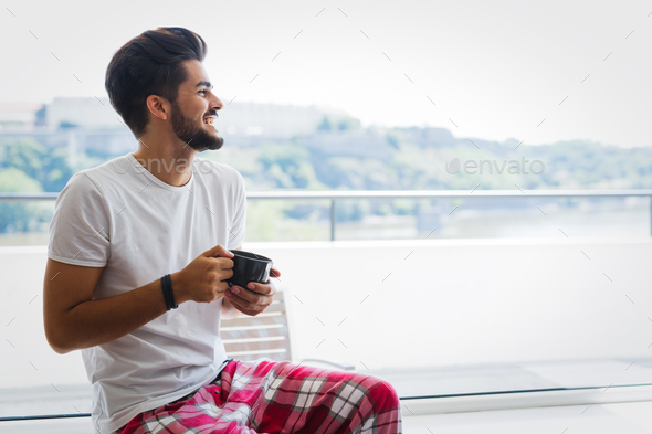 Young man drinking coffee at home in morning - Stock Photo - Images