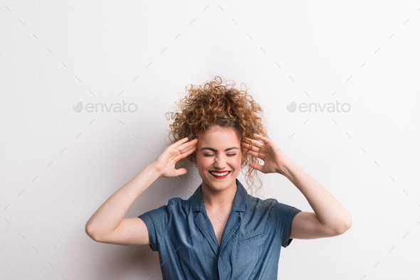 Young beautiful happy woman in studio, hands on temples. - Stock Photo - Images