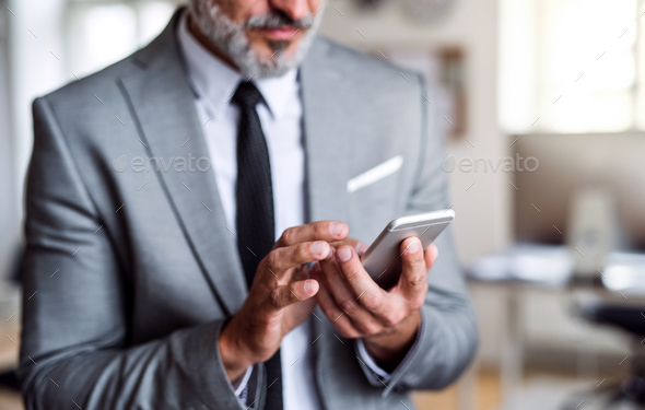 A midsection of businessman standing in an office, using smartphone. - Stock Photo - Images