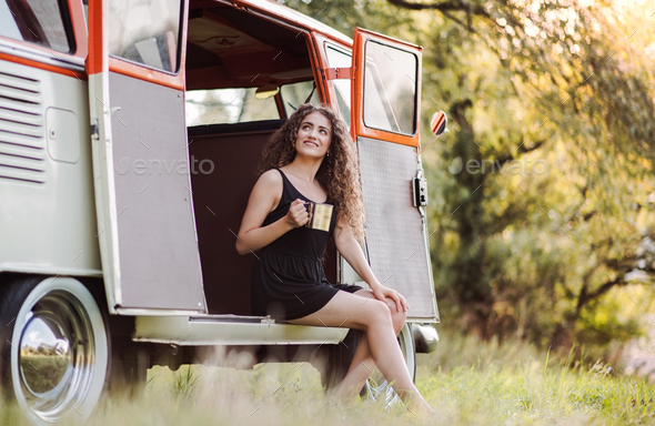 A young girl sitting in the boot of a car on a roadtrip through countryside. - Stock Photo - Images