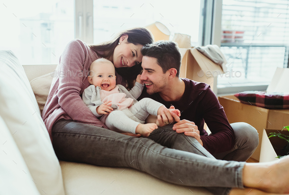 A portrait of young couple with a baby and cardboard boxes moving in a new home. - Stock Photo - Images