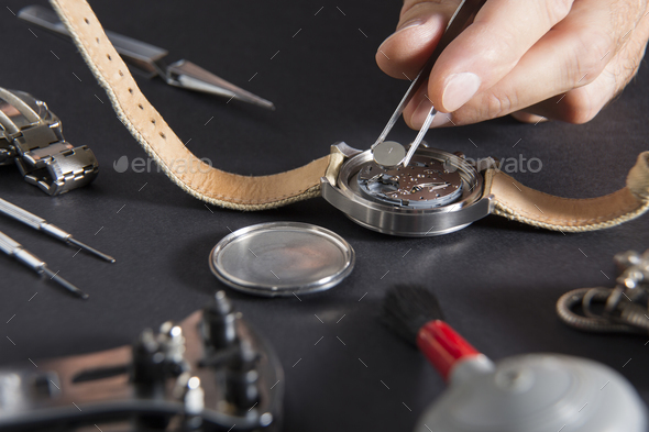 Detail of the work of a watchmaker who replaces a battery - Stock Photo - Images