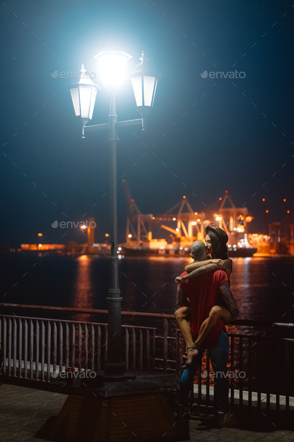 Guy and girl hugging each other on a background of the night port - Stock Photo - Images