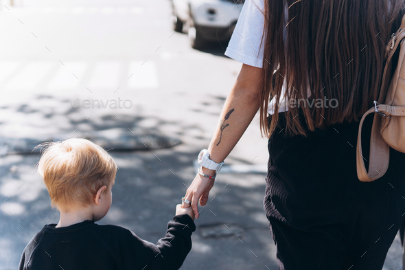 Back view of mother and her little son outdoors in city - Stock Photo - Images