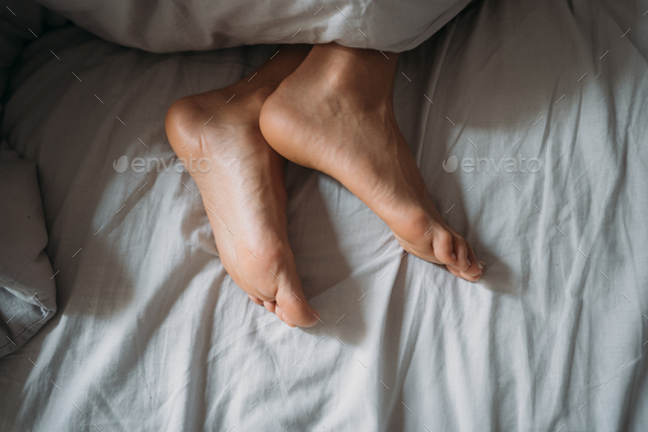 Close-up woman feet alone in white bed - Stock Photo - Images