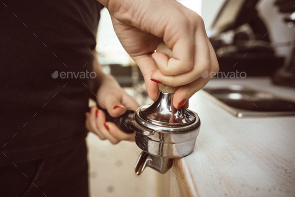 Barista presses ground coffee using tamper. Close-up view on hands - Stock Photo - Images
