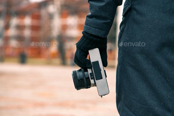 Hipster female photographer holding vintage SLR camera on street - Stock Photo - Images