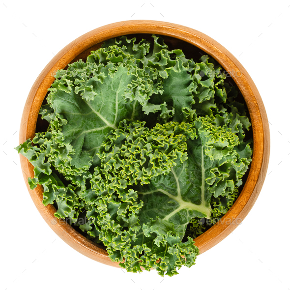 Fresh curly kale leaves in wooden bowl over white - Stock Photo - Images