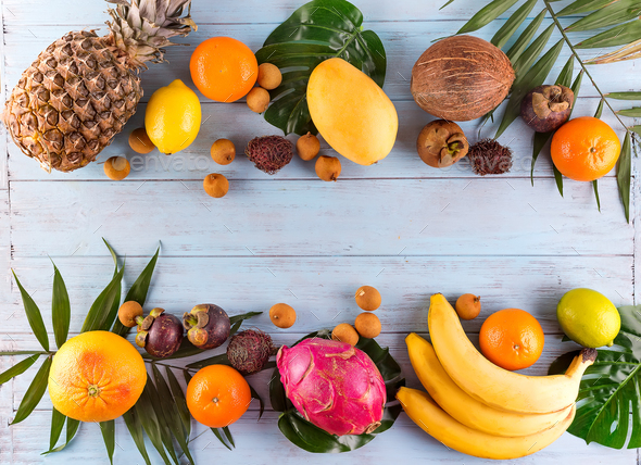 Healthy rainbow tropical fruits frame with palm leaves on blue wooden table, top view, copy space - Stock Photo - Images
