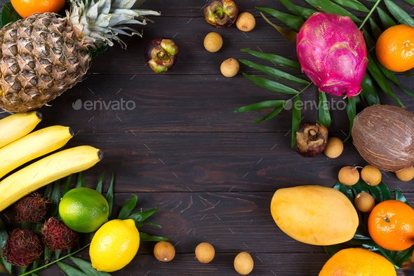 Tropical fruits frame with palm leaves on a dark wooden background, flat lay copy space - Stock Photo - Images