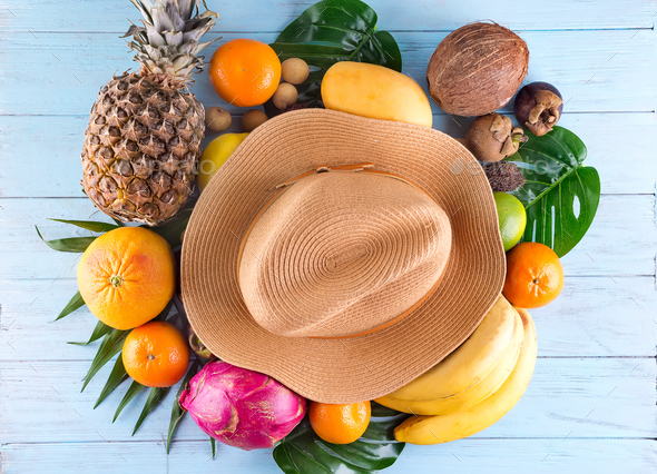 Summer composition. Tropical palm leaves, hat, many fruits on blue wooden background. Summer concept - Stock Photo - Images