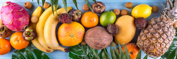 Healthy rainbow tropical fruits banner with palm leaves on blue wooden table, top view - Stock Photo - Images
