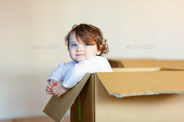 Toddler baby girl sitting inside brown cardboard box. - Stock Photo - Images