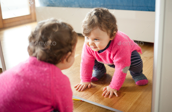 Toddler baby girl playing with mirror in the bedroom - Stock Photo - Images