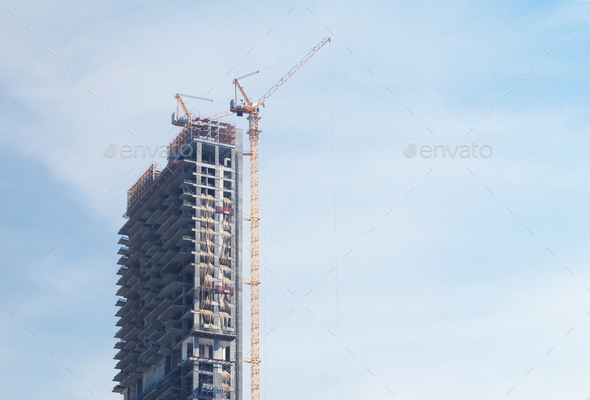 Skyscraper under construction with crane on blue sky background - Stock Photo - Images