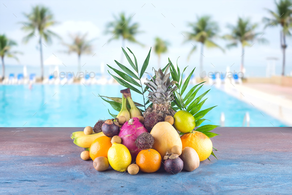 Assorted tropical fruits on the beach orange , pineapple, lime, mango, dragon fruit, orange, banan - Stock Photo - Images