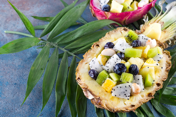 Exotic fruit salad served in half a pineapple on palm leaves on stone background. Healthy food - Stock Photo - Images