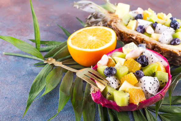 Exotic fruit salad served in half a dragon fruit and pineapple with palm leaf on stone background - Stock Photo - Images