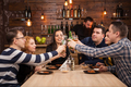 Happy friends group drinking beer and eating pizza at bar restaurant - PhotoDune Item for Sale