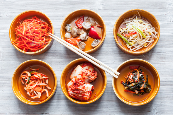 chopsticks above various appetizers in bowls - Stock Photo - Images