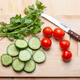 cucumber slices, parsley and tomatoes on cutting board with knife - PhotoDune Item for Sale