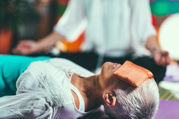 Senior woman on a guided meditation class - Stock Photo - Images