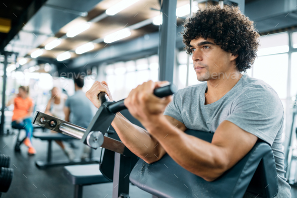 Determined male working out in modern gym - Stock Photo - Images