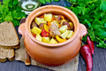 Roast meat and potatoes in clay pot on dark board - PhotoDune Item for Sale