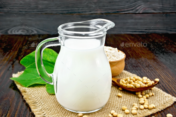 Milk soy in jug with flour on dark board - Stock Photo - Images