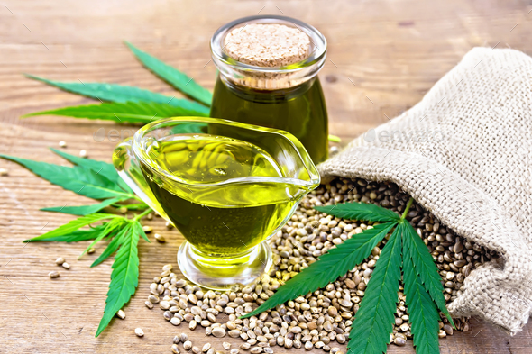 Oil hemp in sauceboat and jar on old board - Stock Photo - Images