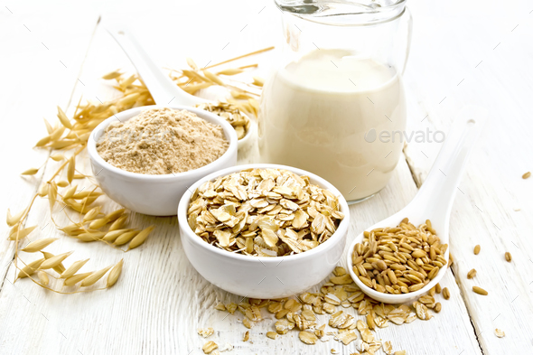 Oat flakes with flour and milk on white wooden board - Stock Photo - Images