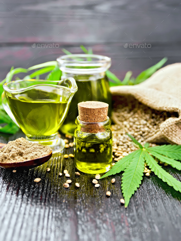 Oil hemp in two jars and sauceboat on dark board - Stock Photo - Images