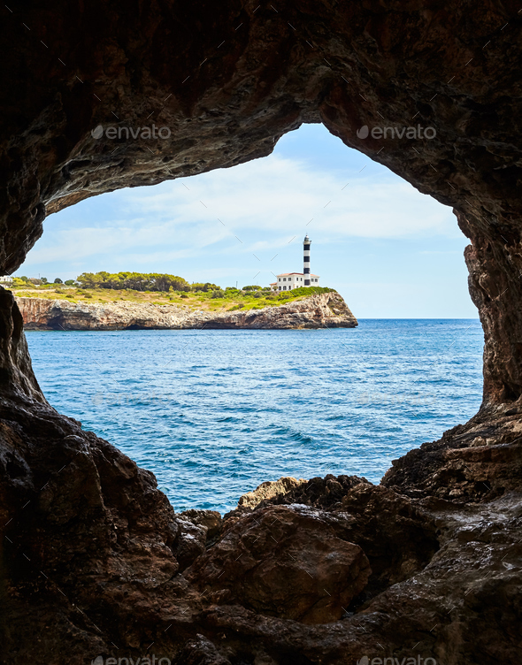 Portocolom Lighthouse seen from a cave, Mallorca. - Stock Photo - Images