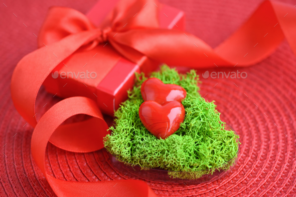 Valentines Day background. Hearts in green moss with red gift bo - Stock Photo - Images