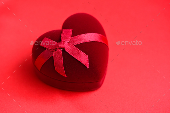 Heart-shaped gift box on red satin fabric background. Valentines - Stock Photo - Images