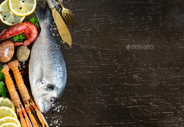 Fresh dorado fish, seafood and vegetables on a dark background - Stock Photo - Images