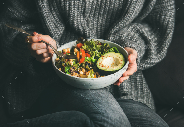 Woman in sweater eating fresh salad, avocado, beans and vegetables - Stock Photo - Images