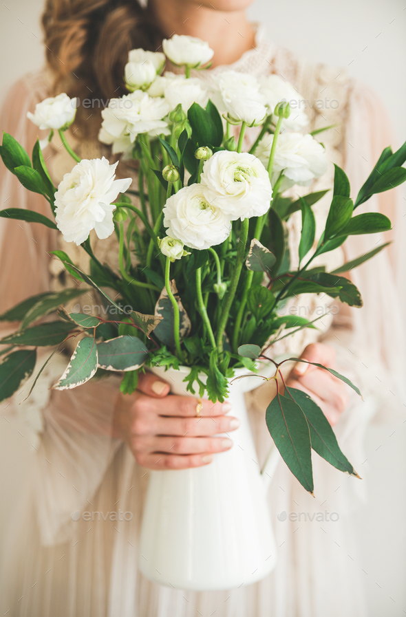 Spring white buttercup flowers in hands of woman - Stock Photo - Images
